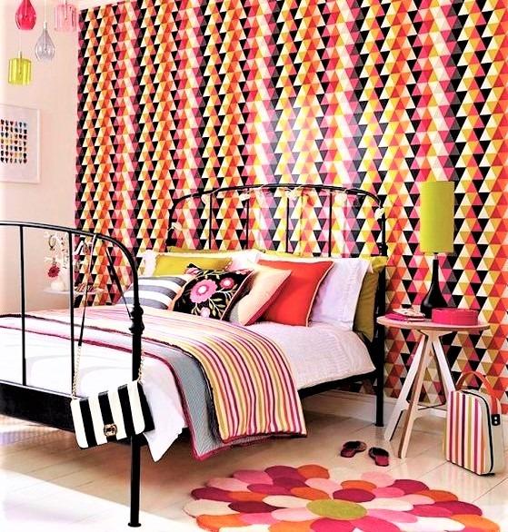 camera da letto con letto in ferro battuto nero e cuscini colorati