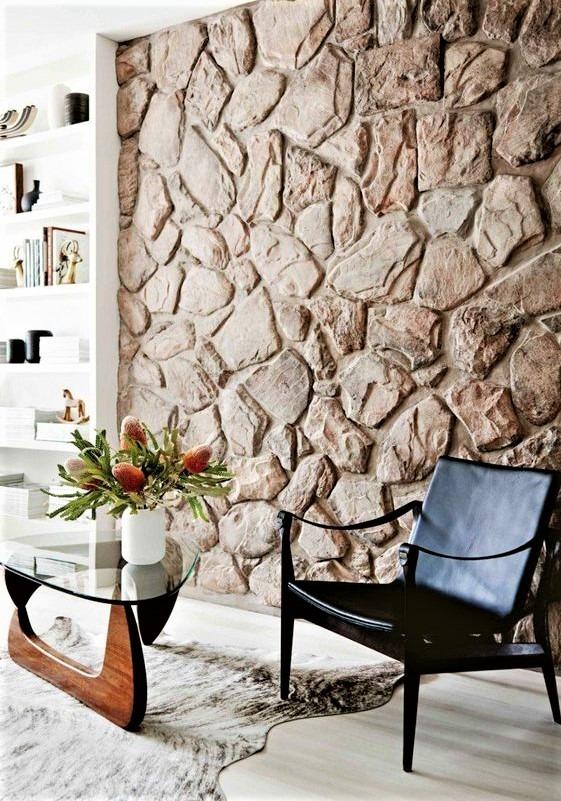 muro effetto pietra con poltroncina nera