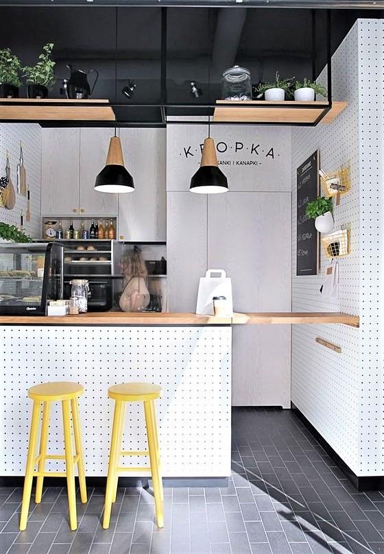 cucina con sgabelli gialli e luci pensili nere