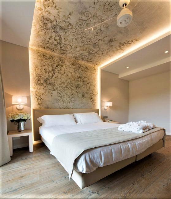 grande letto bianco con carta da parati damascata